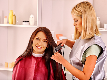 haircutter: Woman at hairdresser with iron hair curler.