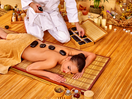 stone therapy: Woman getting stone therapy in bamboo spa