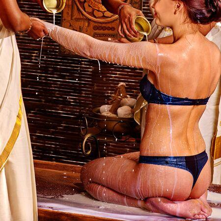 ayurvedic: Woman having Ayurvedic spa treatment. Pouring milk.