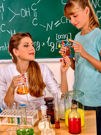 chemistry class: Child and teacher holding flask in chemistry class. Stock Photo