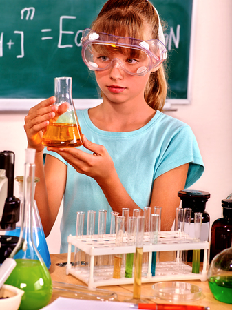 chemistry class: Child in mask holding flask in chemistry class.
