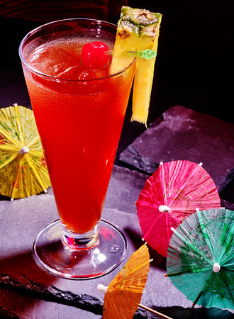 pineapple  glass: Pineapple cocktail with cherry and group umbrella in highball glass .