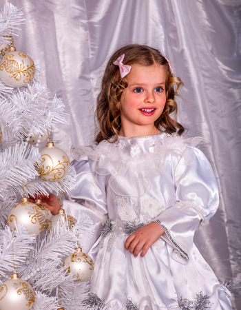 decorate: Child in white dress holding  and decorate Christmas tree.