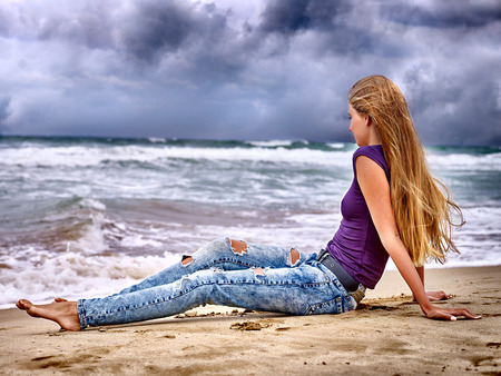 jean: Summer girl sea.  Woman sitting on coast near ocean with waves.