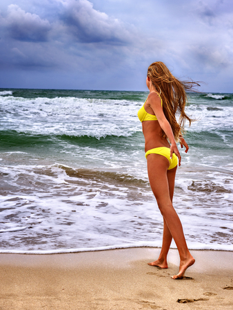 smile girl: Summer girl sea.  Woman in  swimsuit on beach near ocean with waves.