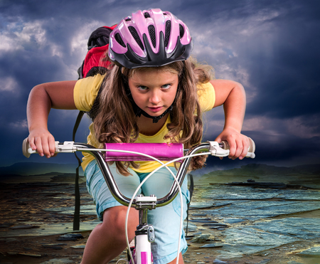 will power: Child girl ride hard on bike to mountain. Stock Photo