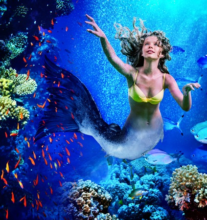 Girl mermaid dive underwater through coral fishes.