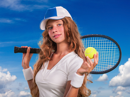 teener: Girl in cap holding tennis  racket and ball on blue sky with clouds.