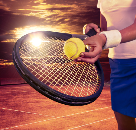 teener: Female hands holding tennis  racket and ball on sky with sun.