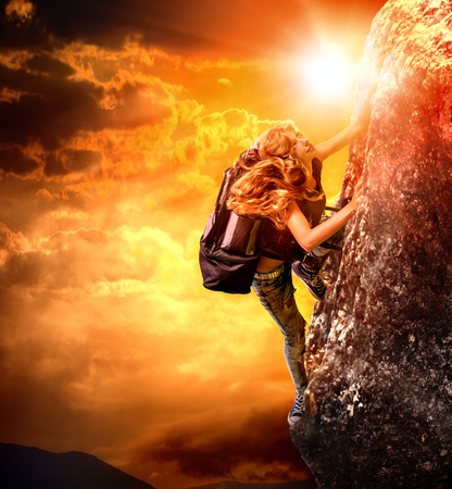 extreme weather: Girl tourists in jeans climbing on rock with backpack. Stock Photo
