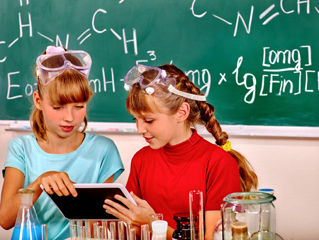 química: Niño que sostiene Tablet PC en la clase de química. Foto de archivo