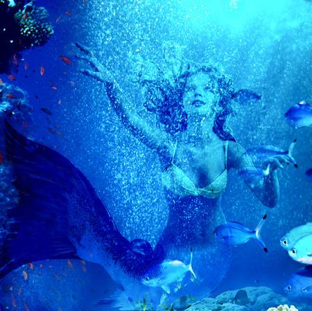 picada: Chica sirena bajo el agua de buceo a través de los peces de coral.