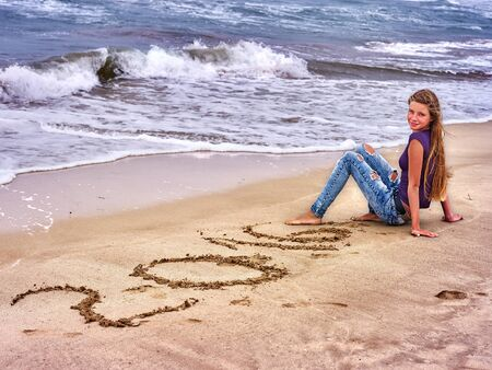 barefoot teens: Summer girl sea.  Woman written in sand  2016 near ocean with waves.