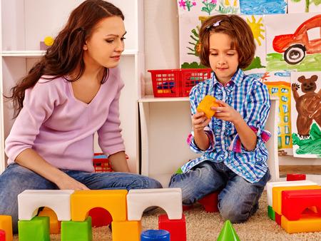 maestra preescolar: Familia con niños jugando ladrillos. Foto de archivo