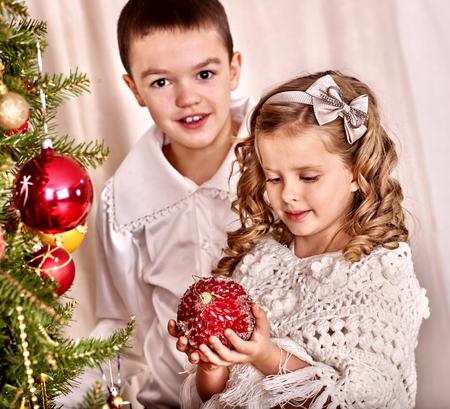niños vistiendose: Niño decorar el árbol de navidad. Infancia estilo retro. Foto de archivo