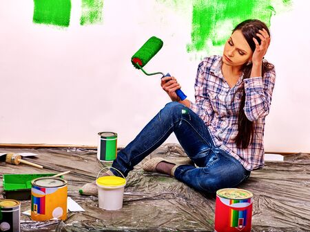 painter girl: Unhappy sad tired woman paint wall at home. Stock Photo