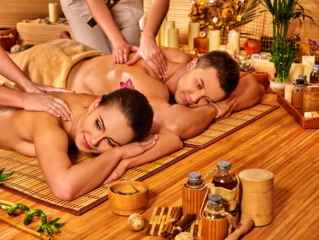 couples therapy: Man and woman relaxing in bamboo  spa interior on wooden floor.