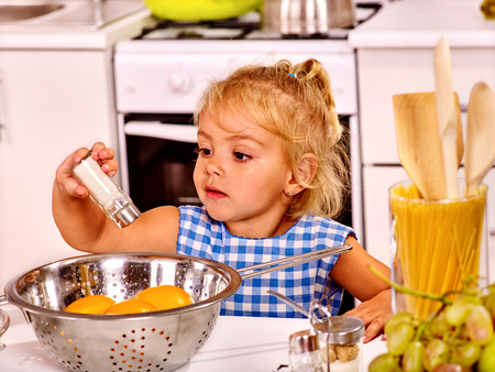 rollingpin: Alone little girl with rolling-pin dough at home kitchen. Stock Photo