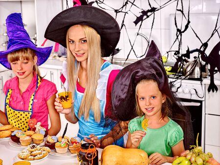 Happy mother with two children preparing halloween food.