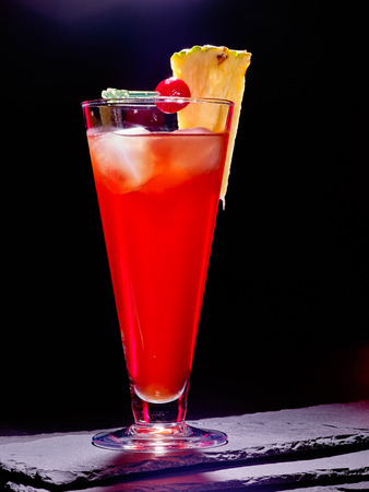 highball: Red  drink  with cherry and pineapple in highball glass . Black Cocktail card 84. Stock Photo