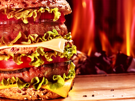 double oven: Double patty hamburger on wooden board on background of fire. Food still life.