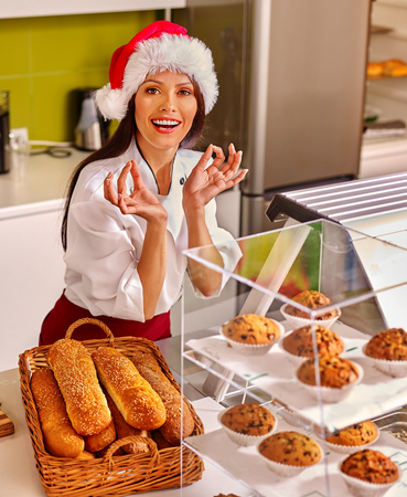 wearing santa hat: Girl wearing  santa hat seller sells fresh bread in store.