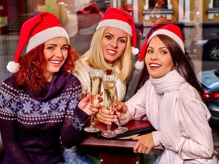 comida de navidad: Tres mujeres hermosas yong en santa sombrero beber champ�n en la cafeter�a.
