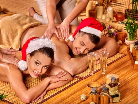 ヘルスケア: 男と女のマッサージを持っているクリスマスの帽子をかぶっています。概念クリスマス スパ。 写真素材
