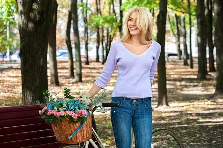 mujeres felices: Hermosa mujer joven en bicicleta en el parque al aire libre.