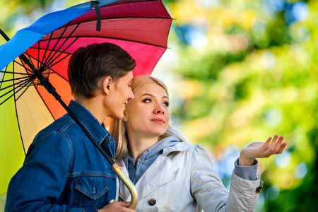 sotto la pioggia: Giovani coppie felici sotto l'ombrello nel giorno di autunno. Amore e coppia concetto e l'idea. Archivio Fotografico