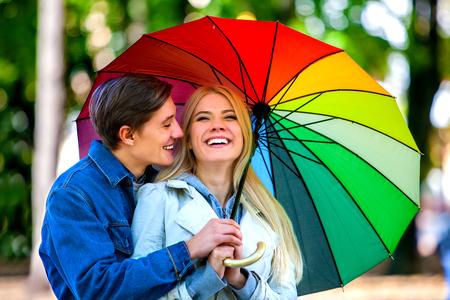 sotto la pioggia: Felice giovane coppia abbracciando sotto l'ombrello nel giorno di autunno. Amore e rapporti di coppia concetto e idea.