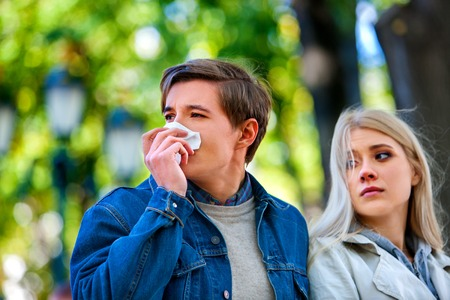 cold season: Man with cold rhinitis on autumn outdoor. Fall flu season. Girl looks with compassion on suffering of loved one.