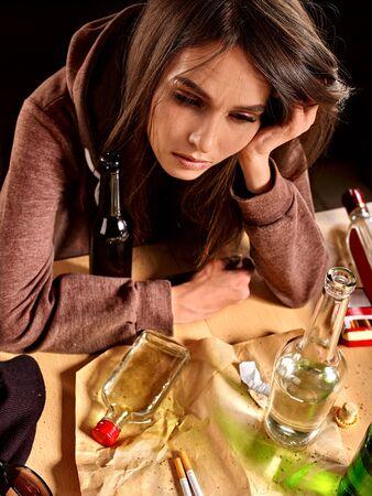 tomando alcohol: Girl in depression drinking alcohol and smokes cigarettes in solitude. Foto de archivo