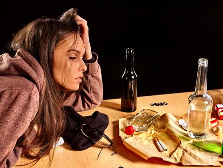 alcool: Fille dans la dépression boire de l'alcool et fume des cigarettes dans la solitude à la table.