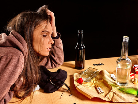 dipsomania: Girl in depression drinking alcohol and smokes cigarettes in solitude at the table.