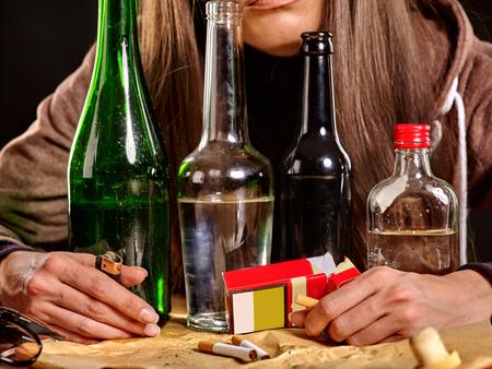 tomando alcohol: Muchacha que bebe alcohol y fuma cigarrillos en la soledad. Botellas y cigarrillos en primer plano