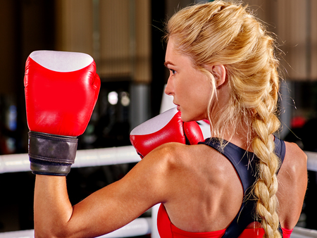 showgirl: Portrait of sport blond girl boxing wearing red gloves. Back view.
