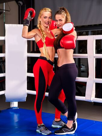 fight arena: Two  women boxer wearing red  gloves posing in ring.