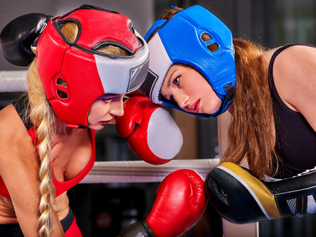 sports venue: Two  women boxer wearing red  gloves and helmet to box in ring. Stock Photo