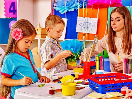 educator: Children with teacher in  preschool  kindergarten painting.