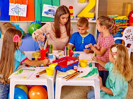 Group children with female teacher in  preschool  kindergarten painting. Imagens - 46948049