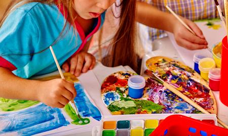 kinder: Cerca de la chica con la pintura del cepillo sobre la mesa en el jard�n de infantes. Foto de archivo