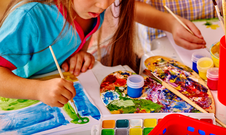 kindergarten: Close up of girl with brush painting on table in  kindergarten . Stock Photo