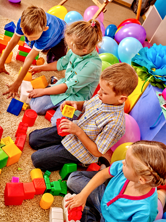 Group children game blocks on floor in kindergarten . Top view.