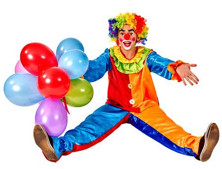 payaso: Feliz cumpleaños payaso sosteniendo un montón de globos y sentado en el suelo. Aislado.