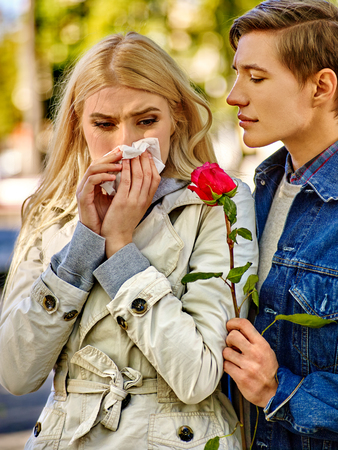 lost love: Betrayal and forgiveness couple. Girl is crying with handkerchief on outdoor. Withered rose as a symbol of lost love Stock Photo