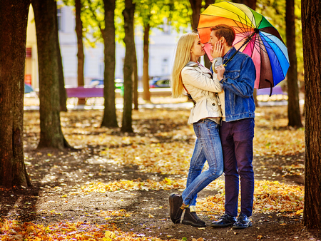 novios besandose: Feliz pareja de jóvenes altura completa besándose bajo el paraguas en día de otoño. El amor y las relaciones de pareja concepto. Foto de archivo