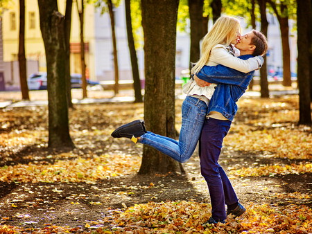 Young couple kissing under umbrella in autumn day. Man hugging and carring on arms girl.