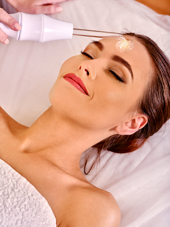 sound therapist: Girl receiving darsonval procedure electric massage at beauty salon. Hardware cosmetology. Stock Photo