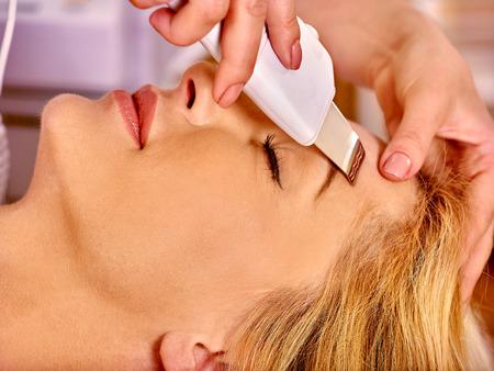 photon: Woman receiving electric facial peeling at beauty salon. Close up.